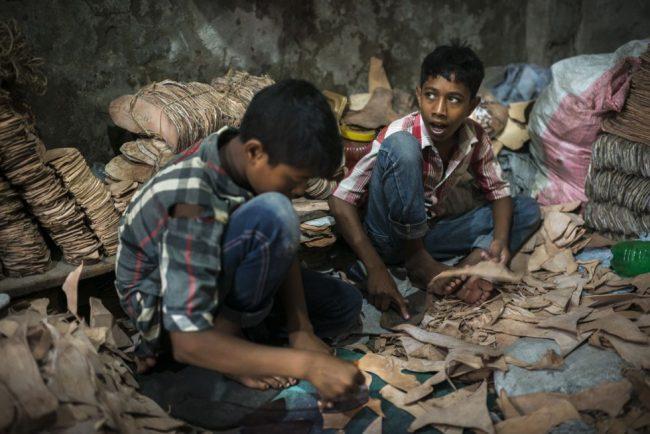 Dos niños trabajando en un taller que fabrica suelas de cuero para zapatos. Ellos manejan cuchillas y herramientas punzantes.